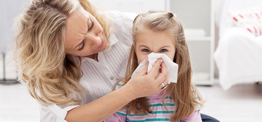 Mom helping young daughter with allergies blow her nose